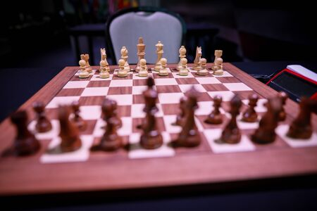 Shallow depth of field (selective focus) image with wooden chess pieces on a wooden table before a professional competition.