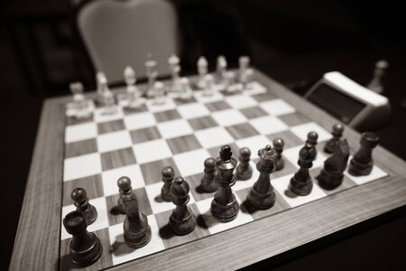 Monochrome shallow depth of field (selective focus) image with wooden chess pieces on a wooden table before a professional competition. Фото со стока - 134750046