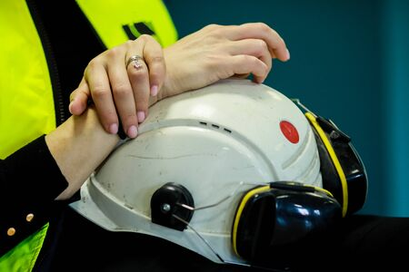 Details with the hands of a female factory worker holding her protective helmet and work headphones.
