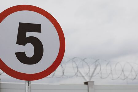 Shallow depth of field (selective focus) image with a speed limit traffic sign in front of a wall with razor wire on top, outside a governmental institution.