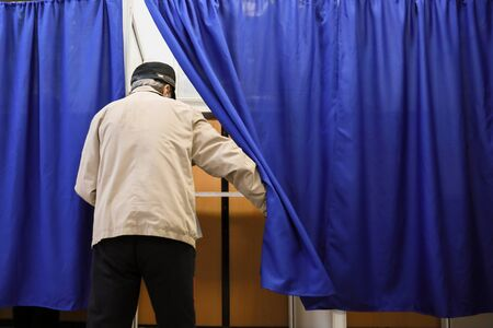 Shallow depth of field (selective focus) image with a man casting his ballot in the first round of a presidential election, in Bucharest, Romania