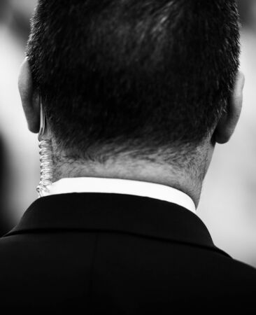 Shallow depth of field (selective focus) image with the coiled tube earpiece a Protection and Guard Service (SPP, Romanian version of the US Secret Service) officer is wearing during a public visit of a dignitary.