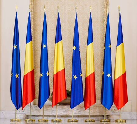 Romanian and European Union flags one next to another inside a hall