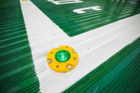 Shallow depth of field image (selective focus) with a green light on the floor of a hospital helipad.