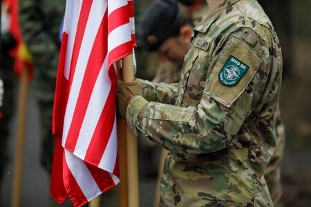 Bucharest, Romania - December 03, 2019: US army soldier holding a flag and having MNDSE (Multi-National Division South-East) insignia.