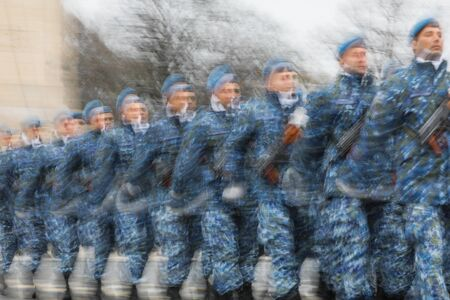 Intentionally panned (lens and shutter speed blur) image of soldiers marching.