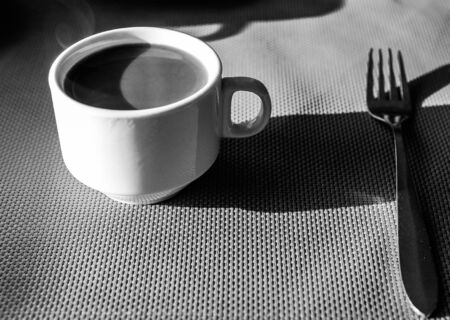 Shallow depth of field (selective focus) image with a cup of hot coffee and a fork on a table during breakfast early in the morning. Black and white