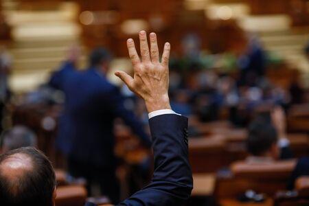 Les membres du Parlement roumain votent en levant la main
