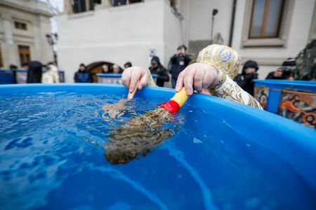 Details with the hands of a high priest of the Romanian Orthodox Church blessing water during the Epiphany mass, with a cross and basil.
