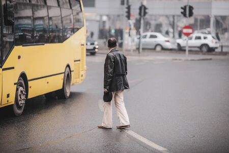 Old man illegally crossing the road in the middle of a crossroad. Stock Photo
