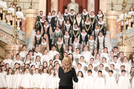Shallow depth of field (selective focus) image with a choir conductor during a live concert.