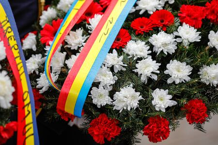 Shallow depth of field (selective focus) image with red gerbera and white chrysanthemum flowers on a funeral wreath with the Romanian flag on the ribbon. Stock Photo