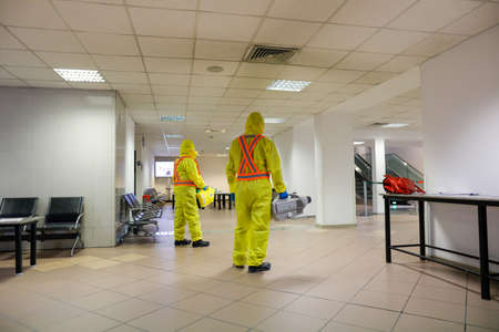 Otopeni, Romania - February 25, 2020: People wearing protective suits spray disinfectant chemicals on the Henri Coanda International Airport to prevent the spreading of the coronavirus.