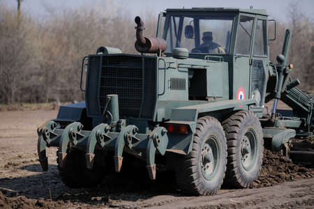 Otopeni, Romania - February 19, 2020: Heavy machinery of the Romanian Army level the ground for a campaign mobile hospital (ROL 2) to treat Covid-19 patients.