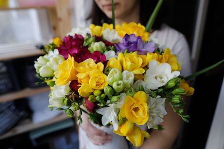 Shallow depth of field image (selective focus) with a woman holding a fresh bouquet of freesias.