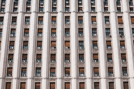 The exterior of an old soviet era style building with window air conditioning machines.