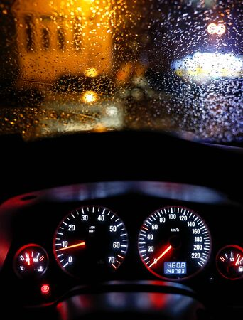Shallow depth of field image (selective focus) with the steering wheel and dashboard lights of a 2010 car and the windscreen with drops of rain. Stok Fotoğraf