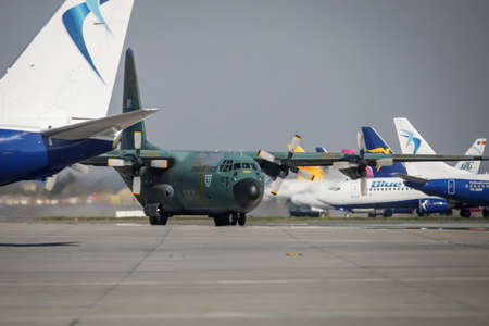 Otopeni, Romania - April 9, 2020: Lockheed C-130 Hercules military cargo plane of the Romanian Air Force on Henri Coanda International Airport between commercial airplanes.