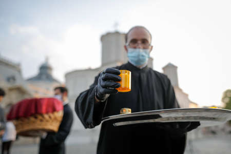 Bucharest, Romania - April 18, 2020: An orthodox christian priest with a surgical mask due to the covid-19 pandemic shares the Holy Light during the orthodox Easter.