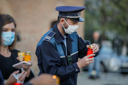 Bucharest, Romania - April 18, 2020: Romanian policeman with a surgical mask due to the covid-19 pandemic takes the Holy Light during the orthodox Easter.
