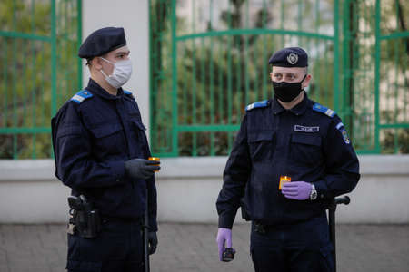 Bucharest, Romania - April 18, 2020: Romanian gendarmes with surgical masks due to the covid-19 pandemic take the Holy Light during the orthodox Easter.