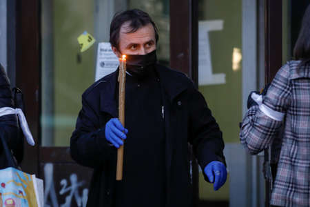 Bucharest, Romania - April 18, 2020: An Orthodox priest wearing gloves and mask due to the covid-19 pandemic lockdown delivers the Holy Light during the orthodox Easter.