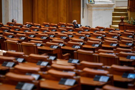 Bucharest, Romania - April 23, 2020: Empty seats and very few MPs in a Romanian Parliament's Chamber of Deputies Meeting during the covid-19 lockdown.