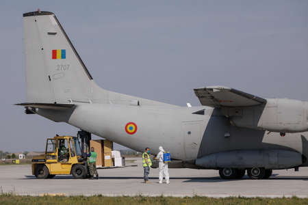 Otopeni, Romania - April 25, 2020: Romanian army personnel unload medical supplies from an Spartan military plane during the covid-19 lockdown. Editorial