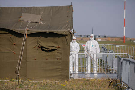 Otopeni, Romania - April 25, 2020: People wearing protective suits for covid-19 near a military tent on an army airport.