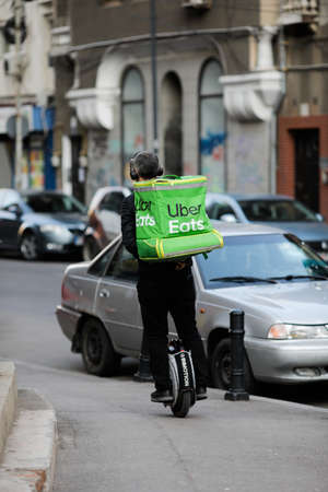 Bucharest, Romania - April 22, 2020: Uber Eats delivery man on monowheel in Bucharest during the covid-19 lockdown.