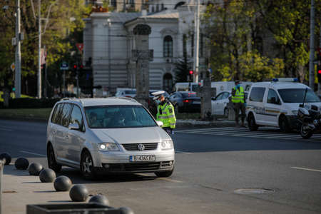 Bucharest, Romania - April 22, 2020: Romanian road police officer pulls over a car to check for the driver's identity papers during Covid-19 lockdown.