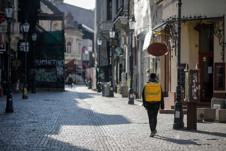 Bucharest, Romania - April 22, 2020: Man carrying a Glovo delivery backpack on the empty streets of Old Town Bucharest during the covid-19 lockdown.