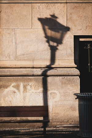 Shadow of a lamp post is casted on the surface of an old building in downtown Bucharest.