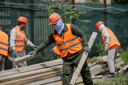 Bucharest, Romania - May 14, 2020: Asian construction workers on a construction site in Bucharest. Editorial