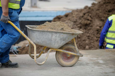 Details with a construction worker pushing a wheelbarrow on a construction site.