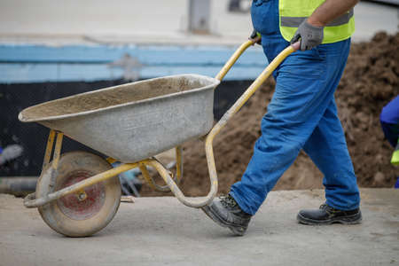 Bucharest, Romania - May 8, 2020: Details with a construction worker pushing a wheelbarrow on a construction site.