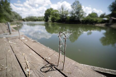 Shallow depth of field (selective focus) image with an old and unused metal support for fishing rods on a wooden pier.