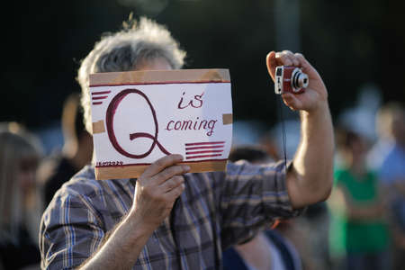 Bucharest / Romania - July 15, 2020: A man takes part at a protest and displays a Qanon message on a cardboard. Editorial