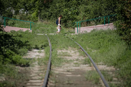Bucharest / Romania - July 14, 2020: Old woman and a little girl walk over an old abandoned railway between heavy vegetation in the city. Editorial
