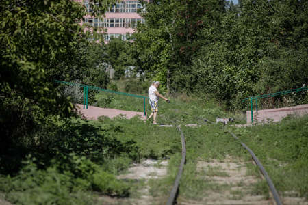 Bucharest / Romania - July 14, 2020: Old woman walks her dog over an old abandoned railway between heavy vegetation in the city. Editorial