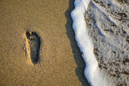 Kid footprint on the sand of a beach during a peaceful late summer sunrise. Stock fotó