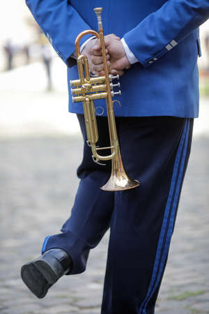 Details with the hands of a military fanfare member holding a brass wind musical instrument. 写真素材