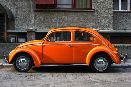 Bucharest, Romania - April 20, 2009: Orange vintage Volkswagen Beetle car on a street in Bucharest. Redactioneel