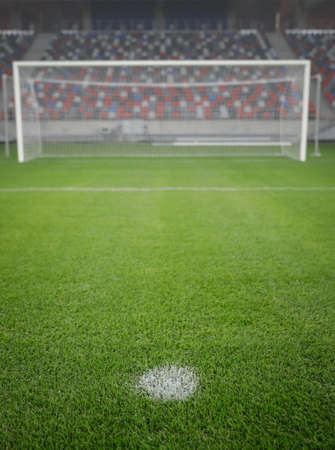 Shallow depth of field (selective focus) image with the penalty kick point on an empty soccer stadium. Фото со стока
