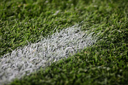 Shallow depth of field (selective focus) image with details of a painted line on a soccer field.