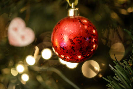 Shallow depth of field (selective focus) image with a red ornament in a plastic Christmas tree. 免版税图像