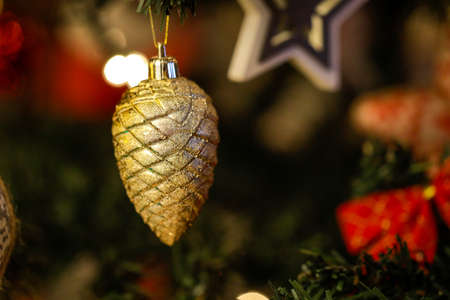 A golden pine ornament in a plastic Christmas tree.