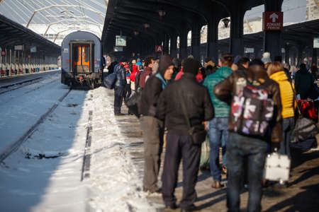Bucharest, Romania - January 5, 2016: People wait for the train in the Northern Railway Station (Gara de Nord) during a cold, sunny and snowy day in Bucharest.
