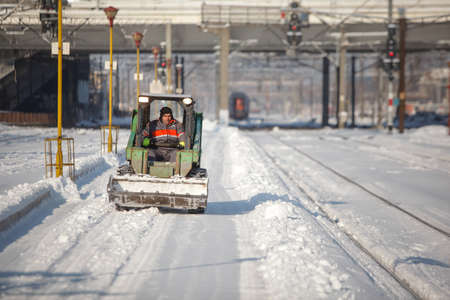 Bucharest, Romania - January 5, 2016: Man driving a small excavator to remove snow from the Northern Railway Station (Gara de Nord) during a cold, sunny and snowy day in Bucharest.