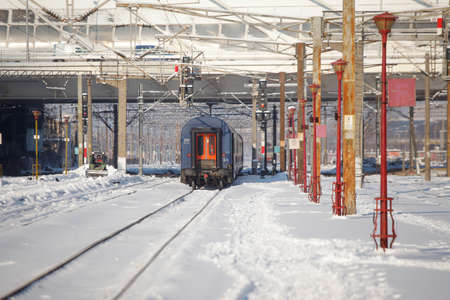 Bucharest, Romania - January 5, 2016: A train is leaving the Northern Railway Station (Gara de Nord) during a cold, sunny and snowy day in Bucharest.
